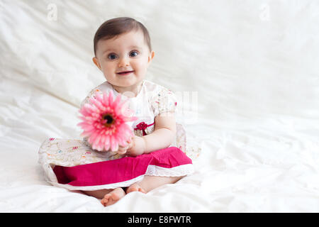 Portrait of cute baby girl (12-17 months) playing with flower - Stock Photo