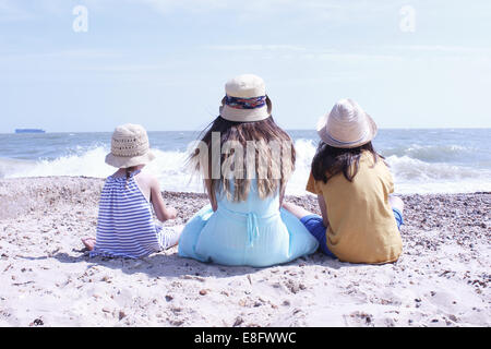 Rear view of three Girls sitting on the beach - Stock Photo
