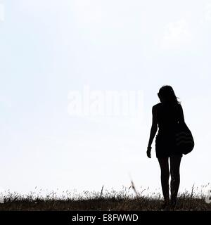 Silhouette of girl standing outdoors - Stock Photo