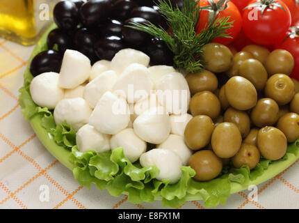 Mozzarella cheese, black and green olives, cherry tomatoes are on green plate. - Stock Photo