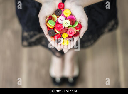 Woman in dress holding buttons - Stock Photo