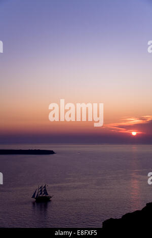 Greece, South Aegean Peripher, Cyclades islands, Santorini, Sailing ship on sea during sunset - Stock Photo