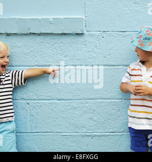 Two boys messing about in front of a blue wall - Stock Photo