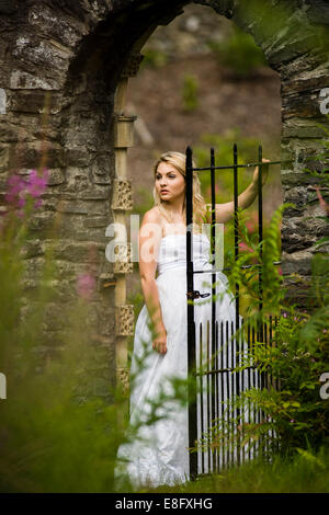 A young blonde woman girl model 'bride' wearing a white ball gown wedding dress standing in a gateway in a stone - Stock Photo