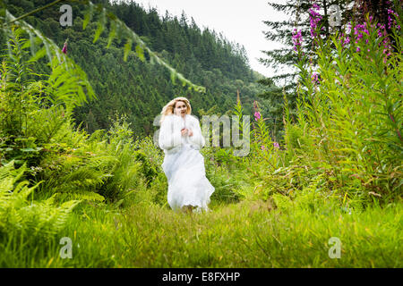 A young blonde woman girl model 'bride' wearing a white ball gown wedding dress running down a path in woodland - Stock Photo