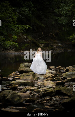 'Trash The Dress': A young blonde woman girl model bride wearing white ball gown wedding dress standing in slow - Stock Photo