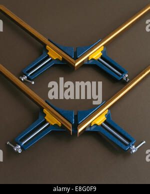 Close-up of gilt picture frames held in metal vices - Stock Photo