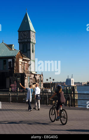 People walking, running, bicycle and fishing in Pier A. Pier A in Battery Park is a building built in 1886 by the - Stock Photo
