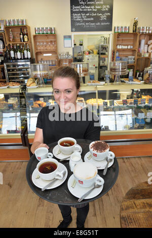 Young waitress carrying a tray of coffee at Di Lieto's Coffee Lounge, The Waterfront, Sovereign Harbour, Eastbourne - Stock Photo