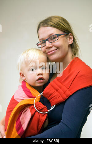 Young mother carrying her 2 year old son in a baby sling, Farnham, Surrey, UK. - Stock Photo