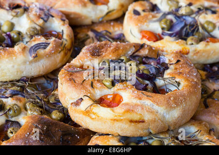 Focaccia, artisan bread, Italian flatbread with herbs, olives and tomatoes. - Stock Photo