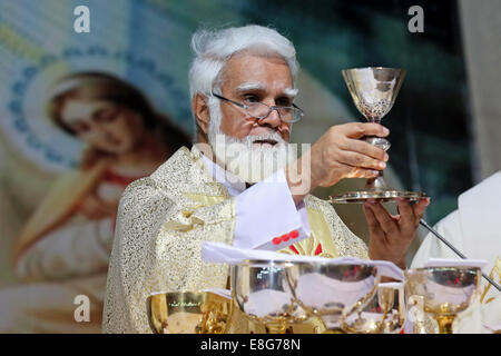 JOSEPH COUTTS, Archbishop of the roman catholic Diocese of Karachi, Pakistan. Raising the goblet with wine/blood - Stock Photo