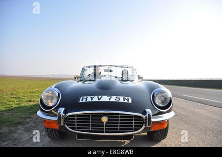 A forty-something couple, wrapped up against the cold, driving a Seventies Jaguar E-type V12 roadster, parked up - Stock Photo