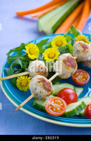 Meatballs on skewers with some fresh vegetables on background - Stock Photo