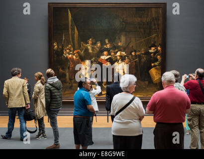 Visitors looking at Rembrandt's The Night Watch in the Rijksmuseum, Amsterdam, the Netherlands - Stock Photo
