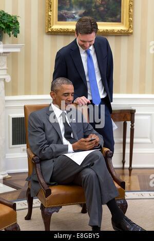 US President Barack Obama looks at photos of Press Secretary Josh Earnest's newborn baby boy, Walker, during a meeting - Stock Photo