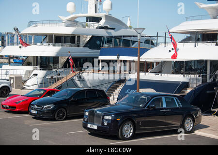 expensive cars parked on wharf in front of luxury yachts in Cannes Harbor on Cote d'Azur French Riviera South of - Stock Photo