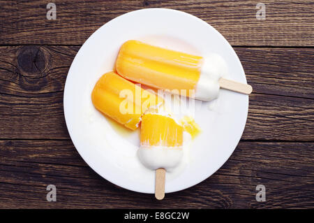 Top view on orange ice cream melted in a plate on wooden table - Stock Photo