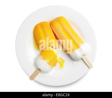 Orange popsicle melted in a plate on white background - Stock Photo
