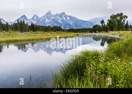 The Grand Tetons with a peaceful reflection over the river but with lots of smoke from a near by forest fire - Stock Photo