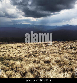 Heavy cloud over field and mountains