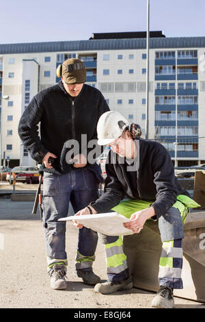 Construction workers analyzing blueprint at site - Stock Photo