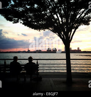 USA, New York State, New York City, Couple sitting on bench at sunset - Stock Photo