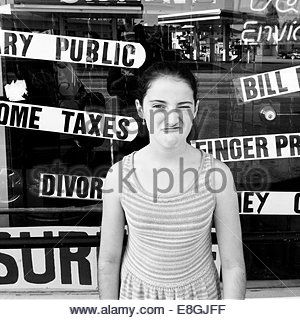 Girl making cheeky face in front of shop window - Stock Photo