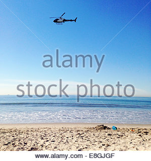 Helicopter flying over beach - Stock Photo