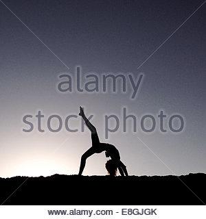 Woman doing yoga at beach at dawn - Stock Photo