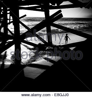 silhouette of boy walking under the pier, Santa Monica, California, America, USA - Stock Photo