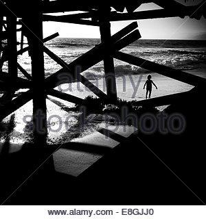 silhouette of boy walking under the pier, Santa Monica, California, America, USA - Stock Photo