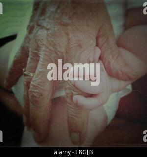 Grandmother holding baby's hand - Stock Photo