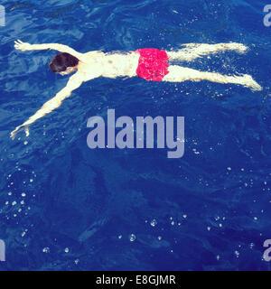 Man swimming in sea face down - Stock Photo