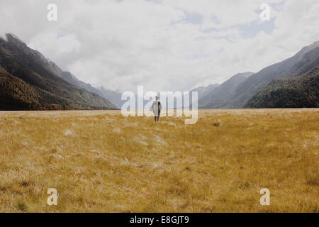 New Zealand, Man standing in grassy field, mountains in background - Stock Photo