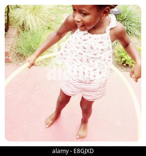 Girl playing with a hula hoop - Stock Photo