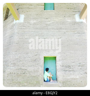 USA,  California, San Francisco, Golden State Park, Woman sitting in old windmill's window sill - Stock Photo