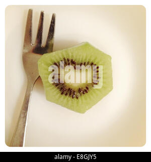 Kiwi fruit with heart shape seeds and fork - Stock Photo