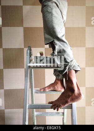 Indonesia, Jakarta Special Capital Region, Jakarta, Man standing on ladder - Stock Photo
