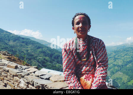Portrait of woman sitting on stone wall in mountains - Stock Photo