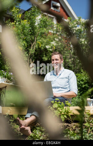 Happy mid adult man with laptop relaxing on terrace - Stock Photo