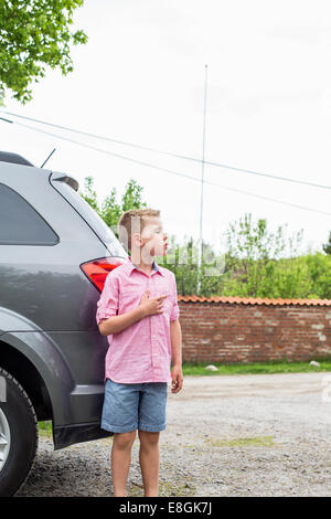 Boy standing in front of car on street - Stock Photo