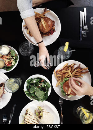 People enjoying burgers and  wraps with salad - Stock Photo