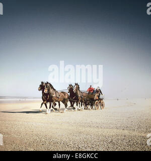 Horses and cart on beach - Stock Photo