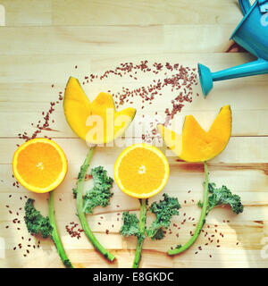 Conceptual watering can watering flowers - Stock Photo