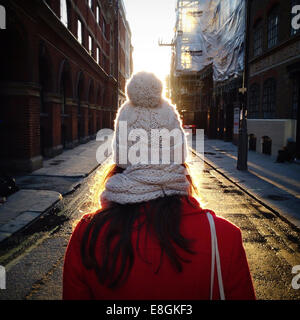 Rear view of woman standing in the middle of the street, Soho, London, England, UK - Stock Photo