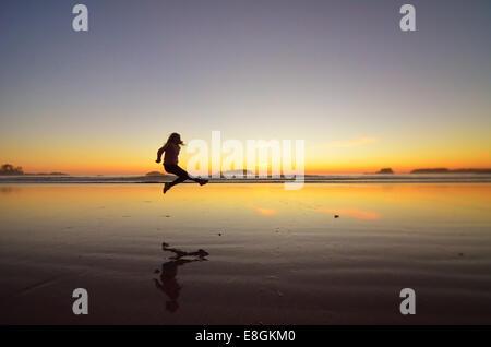 Canada, British Columbia, Alberni-Clayoquot Regional District, Tofino, Young girl jumping on beach - Stock Photo