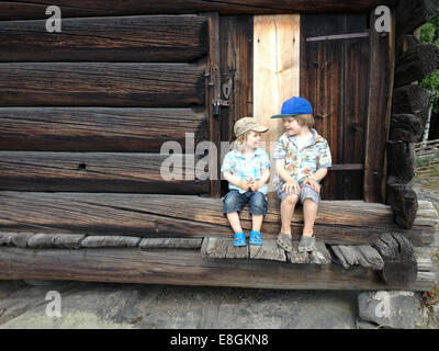 Two boys sitting on porch steps talking - Stock Photo