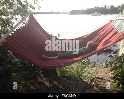 Little Boy Resting In Hammock On A Beautiful Summer Day By The Water - Stock Photo