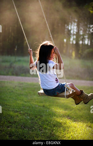 Smiling girl sitting on a rope swing in the garden, Mississippi, USA